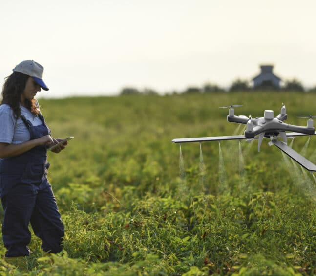 Female farmer using a drone to spray her crops