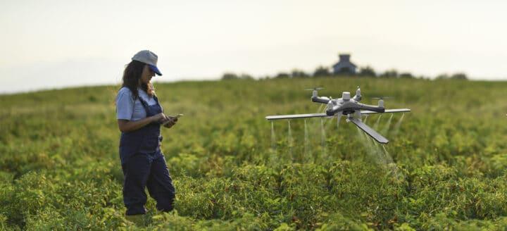 Female farmer using a drone to spray her crops