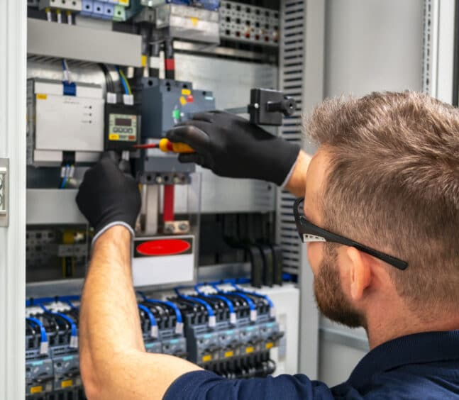 Electrician working at electric panel