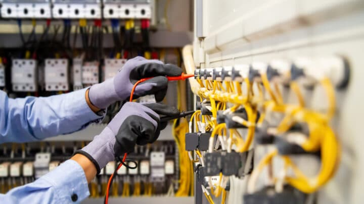 Electrical engineer using digital multi meter measuring equipment to checking electric current voltage.